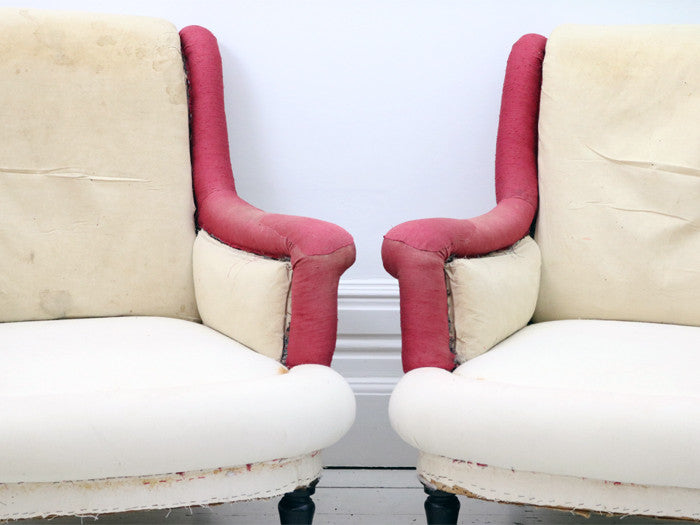 A pair of antique French scroll back armchairs