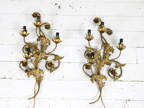 A large pair of gold metal relief wall lights