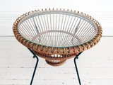 A 1950's rattan table with glass top on tripod legs by Franco Albini