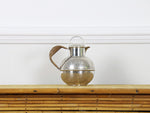 A 1950's etched silver plated tea pot with rattan handle
