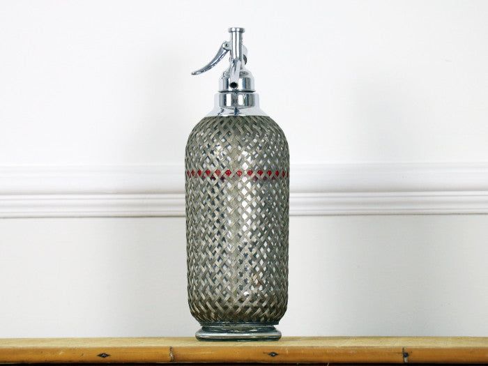 A 1950's wire mesh soda siphon