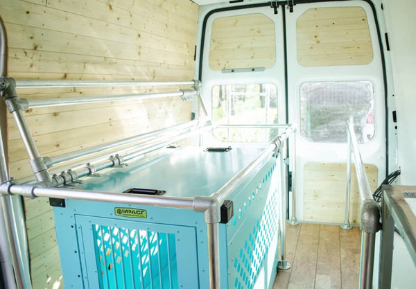 teal stationary impact dog crate as bed in conversion van