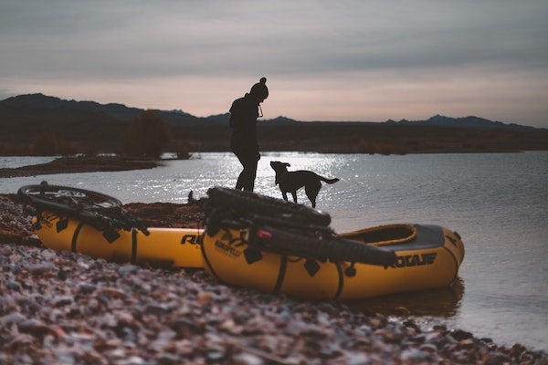 silhouette of girl and dog in river with pack rafts and bikes on boat