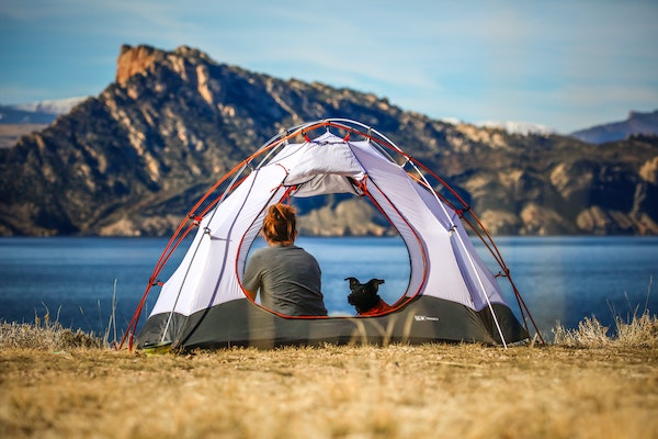 girl and dog sitting in tent looking at view of lake