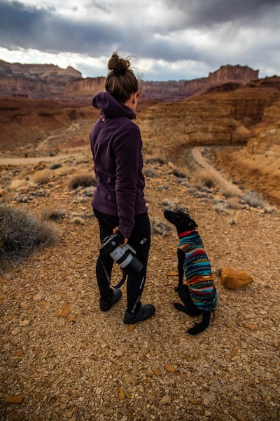 girl holding camera with dog in sweater hiking