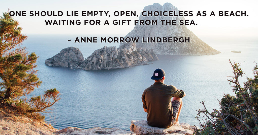 Man with hat sitting on cliff overlooking beach and island. Beach Quote by Anne Morrow Lindbergh