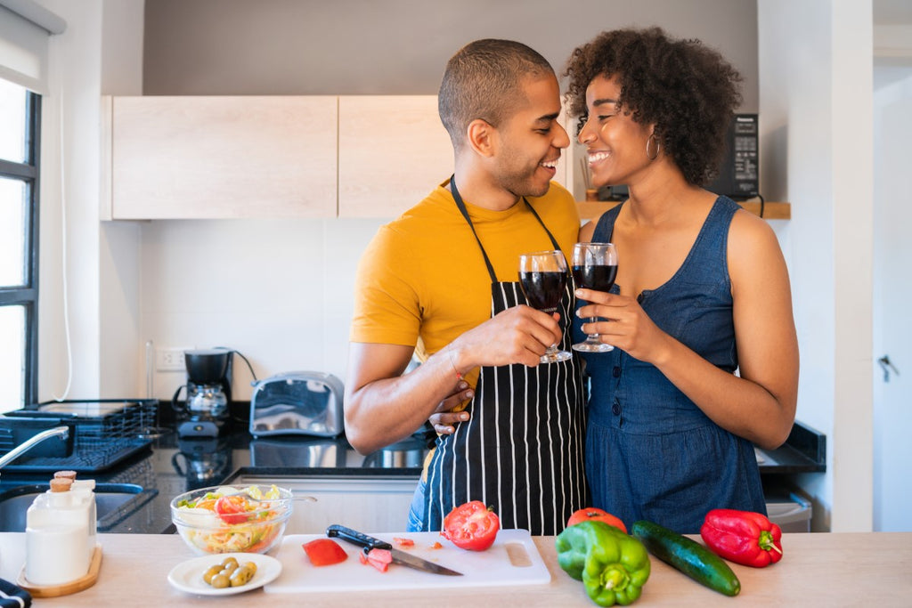 Vegan and omnivore couple cooking together in the kitchen.