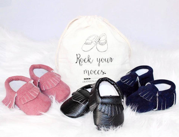 "Soft navy baby suede moccasins with fringe. Comes in a drawstring bag that says, ""Rock your moccs,"" in cursive. Size 0 to 3 months."