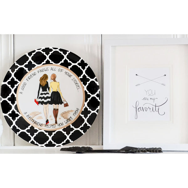 "Ceramic Best Friend Plate with two beautifully dressed girls walking.  It shows the ladies from behind walking down a path, arm in arm. They both have purses. The plate has a black and white damask border.  Around the plate is the quote, ""A good friend knows all of your stories… a best friend helped you write them!"""