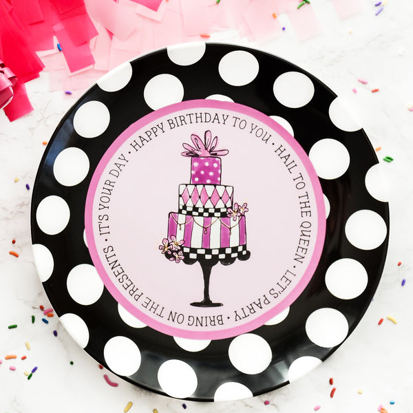 "Ceramic Happy Birthday Plate. It is illustrated with a three tiered pink, white, black, cake that is topped with a bow.  It has peach blossoms on two levels.  It is sitting on a cake stand. The plate has a light pink background and a darker pink circle around that. It has a black and white polka dotted border.  It says, ""Happy Birthday to you • Hail to the queen • Let's party • Bring on the presents • It's your day"" around the plate."