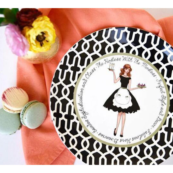 "Ceramic Hostess plate illustrated girl in a black dress and a white apron holding champagne on a tray in one hand and holding a tray with pink cupcakes with cherries on top in the other hand.  It is bordered with black and white damask. Around the plate is a quote, ""The hostess with the mostess • Perfect style and décor • Fabulous hor 'doeurves • Exudes sophistication and class"""