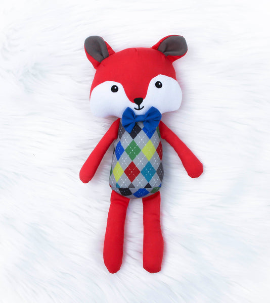 Red soft twelve inch fox toy with blue bow tie, embroidered eyes, nose and mouth. The fox is wearing an argyle pattern. Freddie the Fox who is known for being clever, quick-thinking, and very wise. 100 percent polyester.