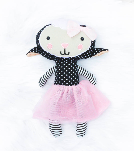 Black, cream, and white twelve inch soft lamb with a pink tutu. The lamb has embroidered eyes, mouth, pink heart-shaped nose, and pink cheeks. The lambs stomach, back of the head and ears and black and white polka-dotted pattern. The legs and arms and black and white striped. The lamb has a light pink bow on her head. She is made of polyester. Meet Lucy the Lamb who is known for being gentle, pure, and simply sweet. Our Loveys are such a cute gift for all ages.