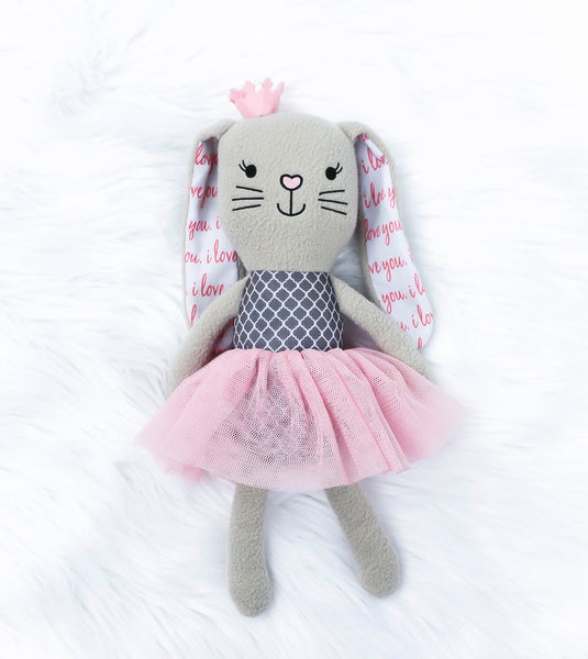 "Gray soft twelve inch rabbit in a pink tutu. The rabbit toy has embroidered eyes, mouth and a pink heart nose. The inside of the bunny ears say, ""I Love you,""in cursive over and over again. The bunny has a gray and white pattern on it's tummy. The rabbit has a pink crown on top of her head. Bella the Bunny is known for being creative, harmonious, and extremely loving."