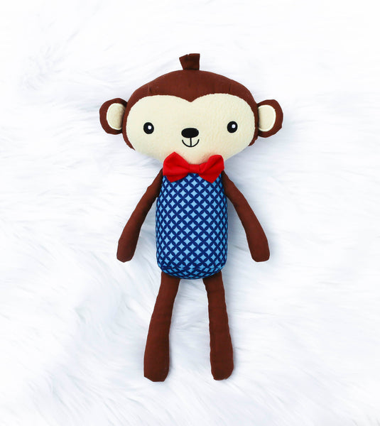 Brown and cream colored soft twelve inch monkey. Blue and light blue argyle on his stomach.  Monkey is wearing a red bow tie. Embroidered black eyes, mouth and nose.