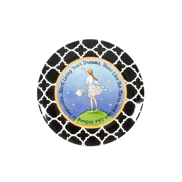 Ceramic Graduation plate illustrated with a girl in a dress reaching for the stars.  She has a graduation hat in her hand. The girl is standing on green grass.  There is a blue background with stars all over.  It is surrounded by a gold circle.  The plate has  a black and white damask border.