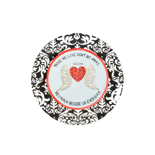 "Ceramic Bereavement Angel Plate illustrated with a red heart with angel wings & a black and white damask border. Around the plate is the quote, ""Those we love don't go away, they walk beside us everyday!"""