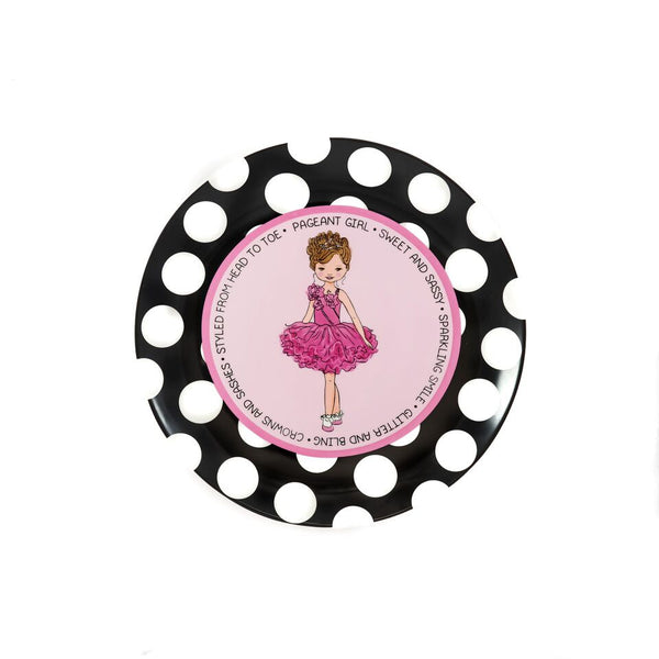"Ceramic Pageant Princess Plate illustrated with a blonde headed little girl in the center. She has a pink ruffly dress on and is wearing a crown. She has pink flowers on the upper part of her dress. The plate has a pink background with a darker pink circle around that. It has a black and white polka dotted border. Around the plate it says, ""Pageant Girl • Sweet and sassy • Sparkling smile • Glitter and bling • Crowns and sashes • Styled from head to toe"""