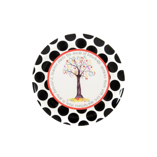 "Ceramic Teacher Plate illustrated with a tree in the center of the plate.   The tree contains letters, numbers, and school supplies. On one branch is an owl.  On the grass below, also has numbers and letters. It has a white background with a red circle around it. It is border with black polka dots and it says, ""A teacher plants the seeds of knowledge, sprinkles them with love, and nurtures them to grow forever!"""