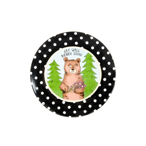"Ceramic Get Well Plate illustrated with a brown bear carrying coneflowers.  There are two green pine trees behind him. Above his head it says, ""Get Well Beary Soon!"" The plate has a black and white polka dotted border."