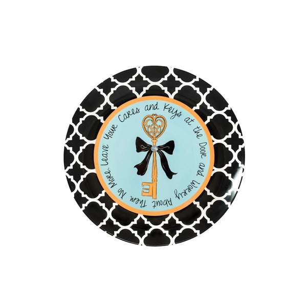 "Ceramic Key Plate illustrated with a gold ornate skeleton key in the center.  The key has a black ribbon tied around it with a jeweled piece in the center. It has a light blue background and a gold circle around that. It is surrounded with a black and white damask border.  ""Leave your cares and keys at the door and worry about them no more"" surround the plate."