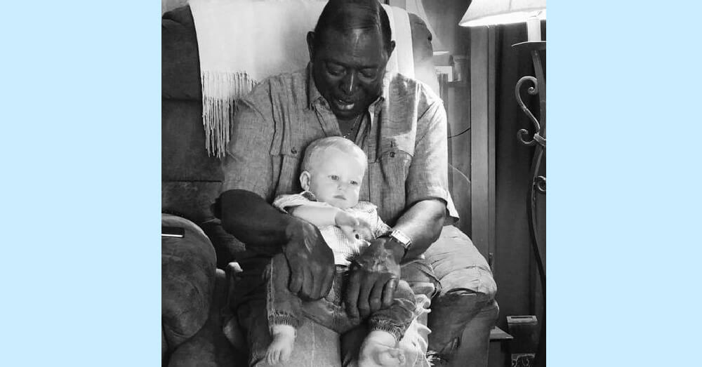 African American man holding Caucasian baby