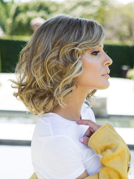 "This wavy wig can be worn in a ""scrunched"" manner or brushed out to create a more voluminous and stylized look."