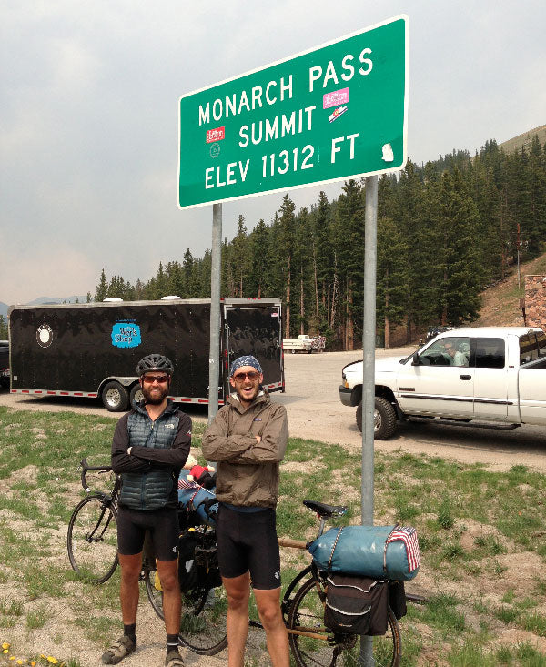 Chris, and his friend Andrew, in front of a sign for the the Monarch Pass