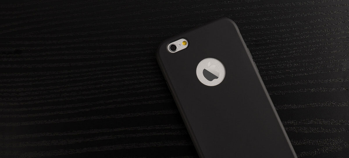 totallee's black iphone case, the doberman, showcasing the apple logo, sitting on a black surface.