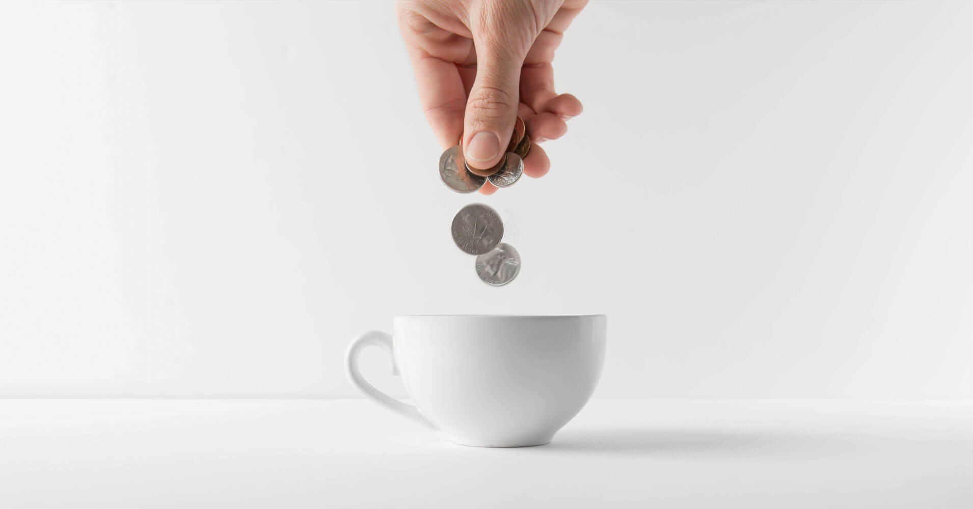 spend less - coins falling in mug