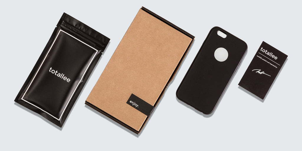 totallee's packaging: an elegant black bag, kraft cardboard box, a black iPhone case, and black warranty card.