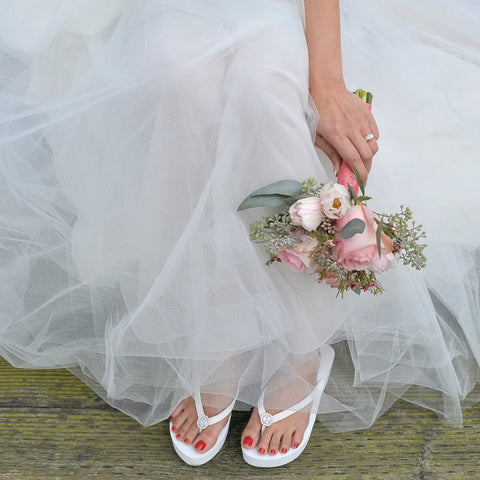 Bride wearing white flip flops with vintage diamond ring