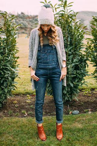 Style your overalls with a beanie, booties, and cardigan.