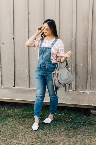 Sandy Chang from sandyalamode.com styles her denim overalls with white loafers and a pink striped ruffle top