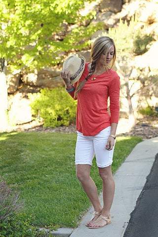 Outfit with 3/4 length red shirt, white bermuda shorts, and sandals.