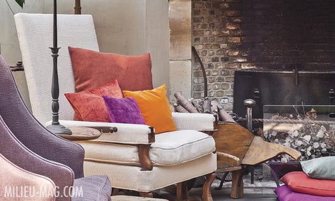 Raspberry colored cushions with violet and tangerine bring color and warmth to the antique armchair by the fire - Walda Pairon