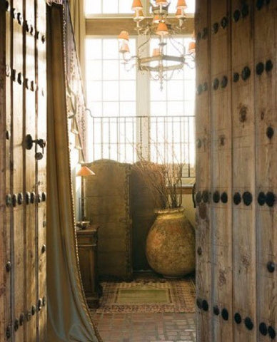 Rustic solid raw timber doors lead into the house, with a lustre and french biot pottery jar