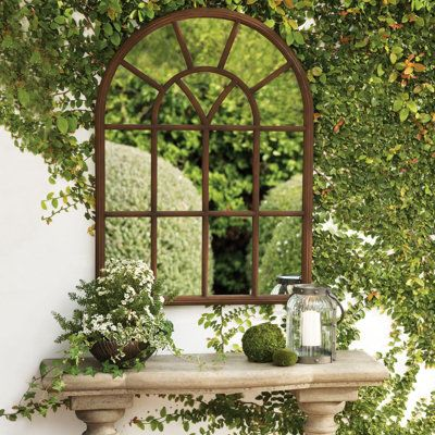 Arched mirror in courtyard marble table creeper ivy green luxury modern farmhouse