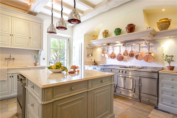 Antique French confit pots displayed in modern French kitchen