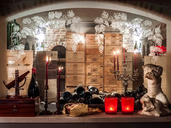 Wine cellar with antique and vintage candlesticks make it a fun and moody space - Walda Pairon