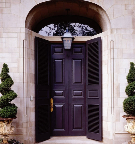 Black front door in Paris with topiary and Medici urns