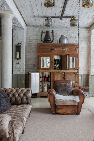 Industrial mid-century loft with french leather club chair and chesterfield sofa