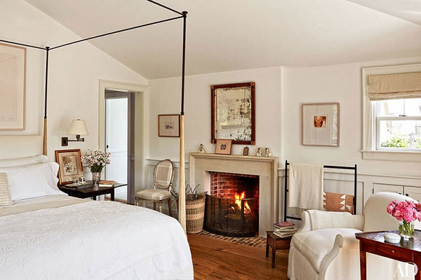 Antique mirror hanging above the fireplace in this Mark Cunningham designed bedroom