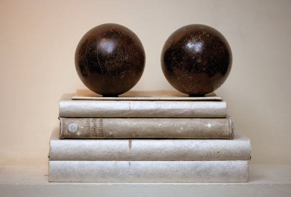 Petanque balls sit on top of vintage books with neutral palette - Walda Pairon