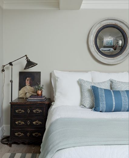 Jenny Wolf - bedroom with round mirror and antique commode