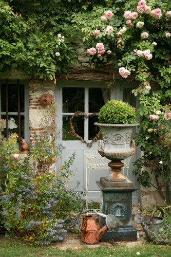 French copper watering can and medici urn on pedestal climbing rose rustic garden