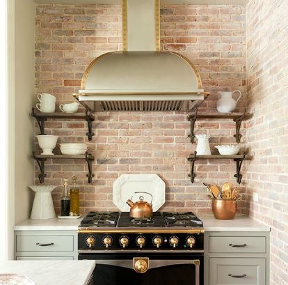 Jenny Wolf - White ceramic pottery collection copper pots in kitchen with exposed brick