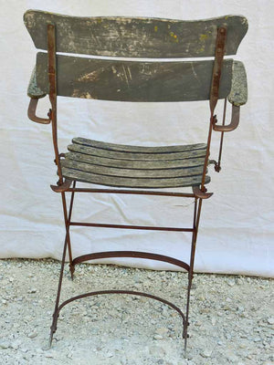 Four antique French iron and timber slatted garden armchairs
