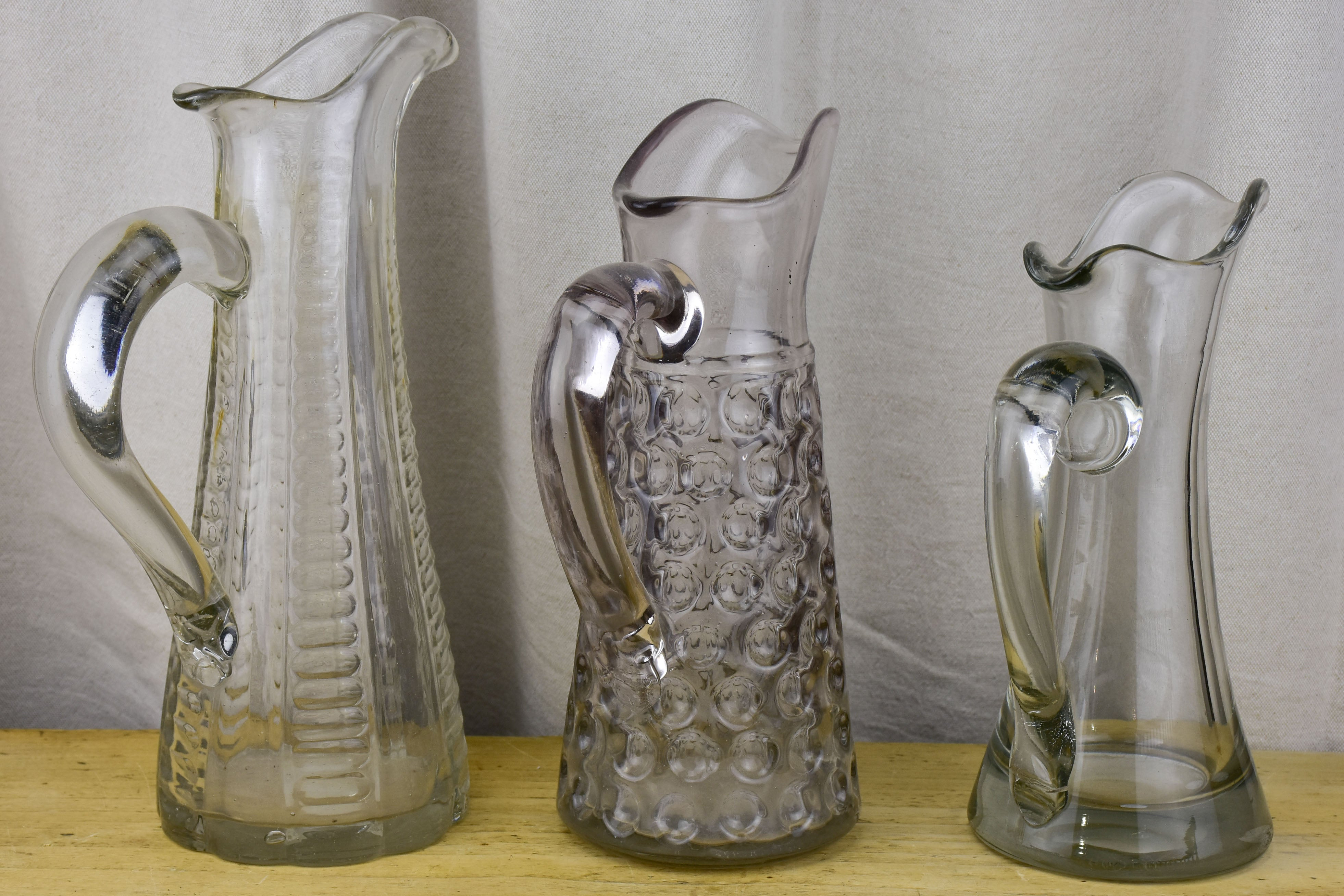 Three antique French pitchers with hand blown glass