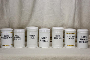 Collection of 7 white antique French apothecary jars with lids